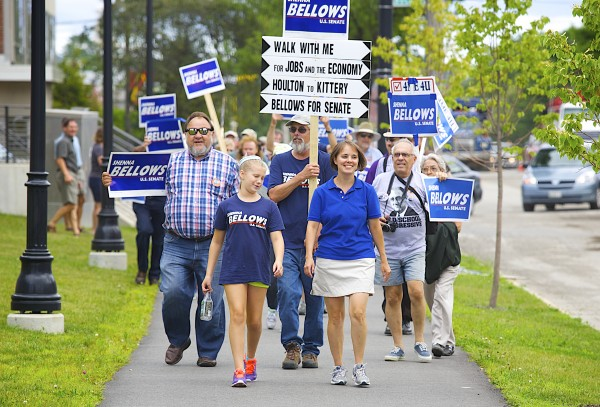 U.S. Senate candidate Shenna Bellows (right) walks in front of a crowd of supporters alongside her niece, Jocelyn Jordan, 10, (left) while making a campaign stop in Bangor on Tuesday as part of Bellows' campaign trek across Maine.