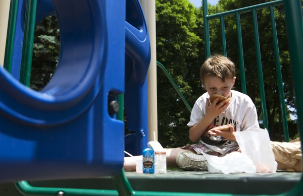 Jacob Reynolds, 7, inspects his ham and cheese sandwich, which was free as part of a summer lunch program, at Second Street Park in Bangor on Thursday.
