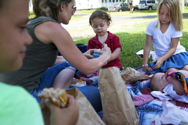 Lisa Boss (second from left) helps her 20-month-old son with his straw while Lauren Boss (right), 9, and Abby Chapman, 6, enjoy their lunches, which are free as a part of a summer lunch program, at Second Street Park in Bangor on Thursday.