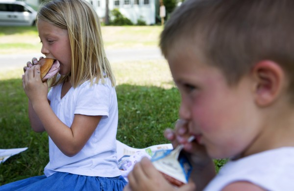 Abby Chapman (left), 6, and Maxwell Hall, 4, enjoy their lunches, which were free as part of their summer lunch program, at Second Street Park Thursday in Bangor.