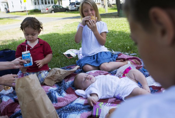 Lauren Boss (right), 9, takes a bite of her ham and cheese sandwich, which was free through a free summer lunch program, while her 20-month-old brother reaches for his milk at Second Street Park in Bangor on Thursday.