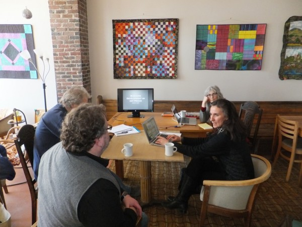 Carol Ayoob (back right) defends her master's thesis in The Whole Potato Cafe and Commons in Presque Isle before her committee of art professors: (from left) Anderson Giles, Owen Smith and Joline Blais.