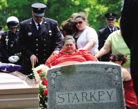 Bonnie Starkey receives support from her family at her husband Brian's grave.