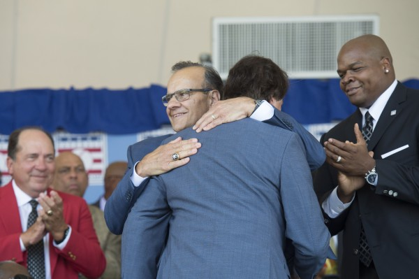 Baseball Hall of Fame inductees Joe Torre (left) and Tony La Russa (center) embrace while fellow inductee Frank Thomas (right) looks on during the class of 2014 induction ceremony Sunday at the National Baseball Hall of Fame in Cooperstown, New York.