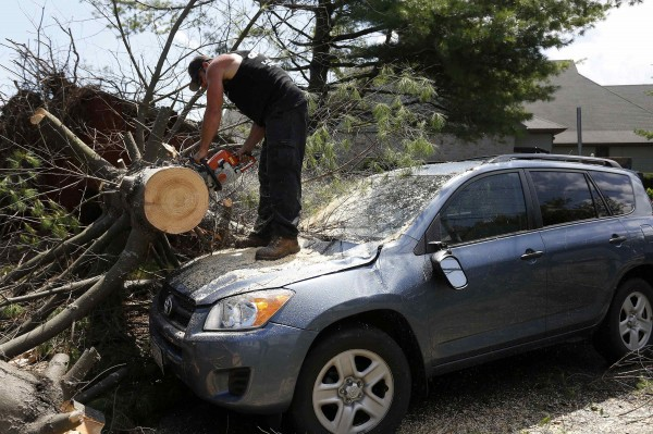 A worker cuts a tree from on top of a storm-damaged car on Beach Street in Revere, Massachusetts, on Monday.