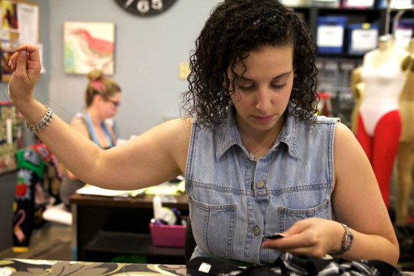 Rachel Soll, assistant costume shop manager at Maine State Music Theatre in Brunswick, sews buttons on a costume Tuesday for an upcoming production of &quotFootloose.&quot