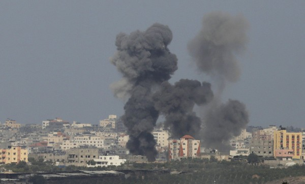 Smoke rises after an explosion in the northern Gaza Strip on Sunday. Thousands fled their homes in a Gaza town on Sunday after Israel warned them to leave ahead of threatened attacks on rocket-launching sites, on the sixth day of an offensive that Palestinian officials said has killed at least 160 people.