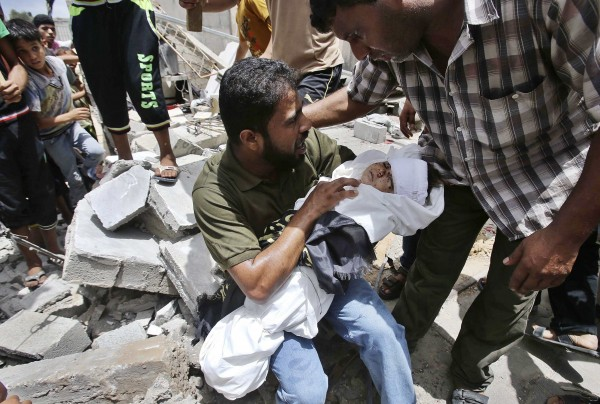 The father of four-year-old Palestinian boy Muayed al-Araj, who hospital officials said was killed in an Israeli air strike on his family's house, carries Muayed's body as he sits on the rubble of his house during Muayed's funeral in Khan Younis in the southern Gaza Strip on Sunday.