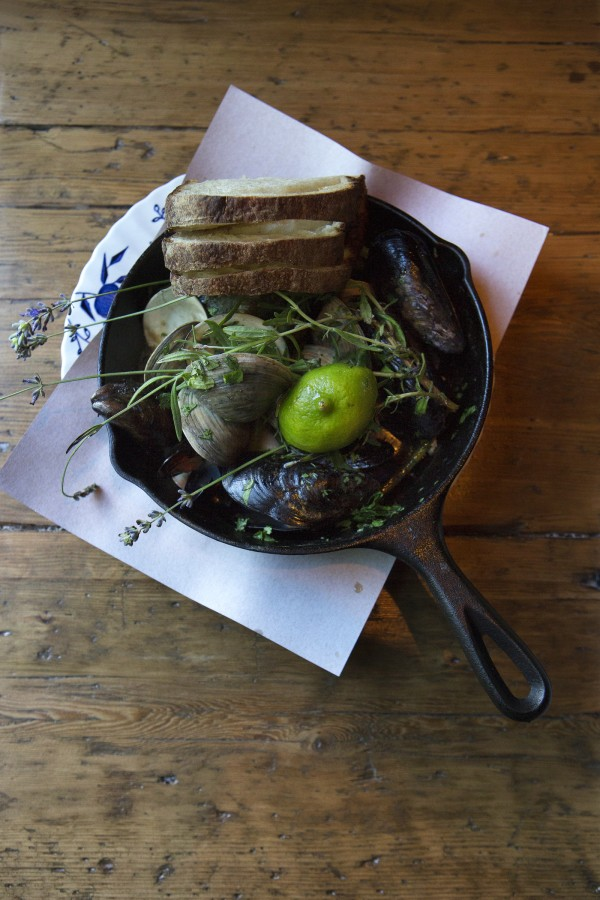 A skillet of mussels and littlenecks with cilantro, lavender, and lime is seen Wednesday at The Lost Kitchen, 22 Mill Street, in Freedom.
