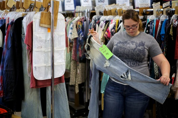 Maine State Music Theatre intern Christina Wann gets a pair of jeans off a rack of potential costumes at the Maine State Music Theatre costume shop in Brunswick on Tuesday.