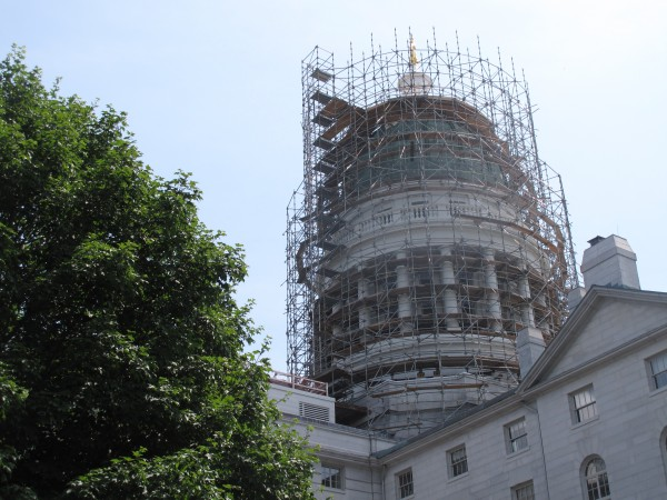 Scaffolding around the State House Dome, seen here Tuesday, will be a regular sight through October, as contractors work to replace the more than 100-year-old weather-damaged and oxidized copper patina with a shiny new one.