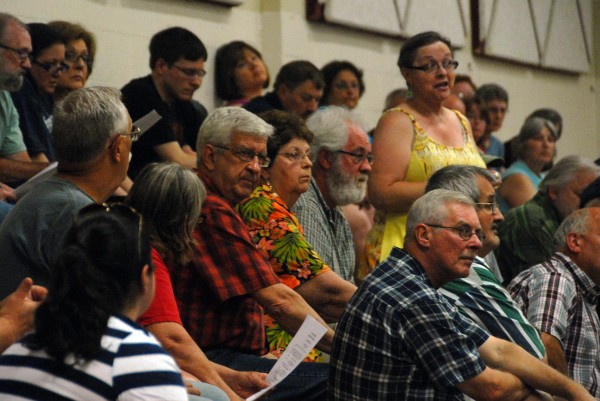 A resident speaks out during a town meeting on Monday at Medway Middle School in Medway.