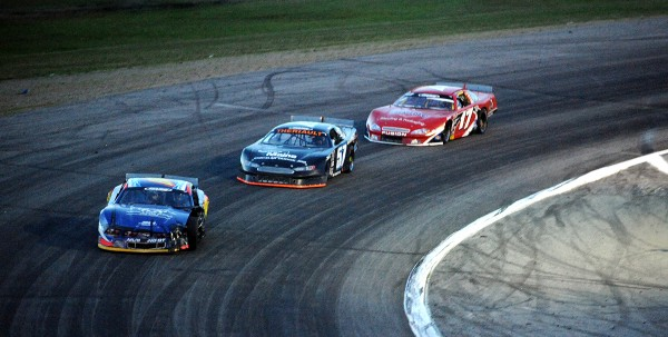 Austin Theriault, center, and Travis Benjamin battle (17) it out for the lead in lap 150 of the Oxford 250 Sunday. Benjamin went on to claim his second straight Oxford 250 victory.