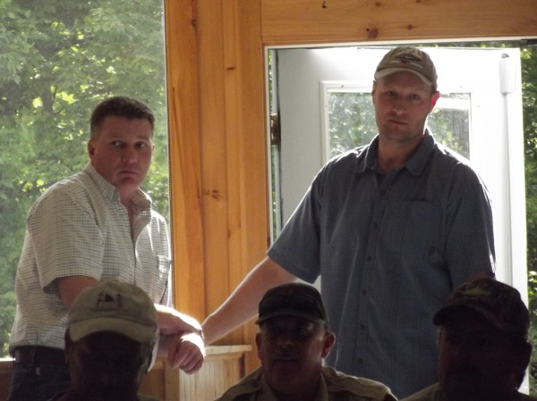 Patrick Keliher (left), Commissioner of the state Department of Marine Resources, and Carl Wilson (right), a department marine scientist, listen to discussion of scallop fishermen in Dennysville recently.