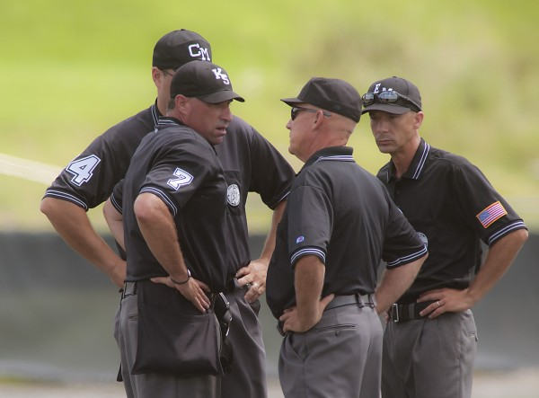 Game officials confer between the mound and second base after a controversial play when Brewer pitcher Kyle Alexander was hit by a line-drive in the seventh inning  of their American Legion playoff game against Staples Crossing at the Winkin Complex at Husson University in Bangor.