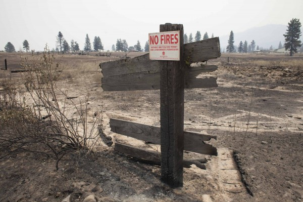 A fire safety sign is seen on the remnants of a fence that was burned by the Carlton Complex Fire near Malott, Washington July 20, 2014.
