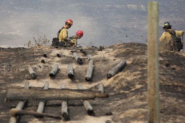Firefighters work in a field near a burnt fence that was hit by the Carlton Complex Fire near Brewster, Washington July 20, 2014.