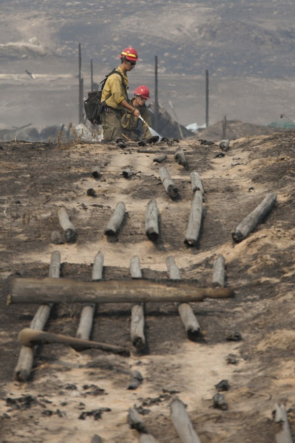 Firefighters work in a field near a burnt fence that was hit by the Carlton Complex Fire near Brewster, Washington July 20, 2014. A massive wildfire raging east of Washington state's Cascade Mountains showed some sign of calming Sunday, with fire crews saying they had slowed the expansion of a wind-whipped blaze that destroyed about 100 homes and displaced hundreds of people.