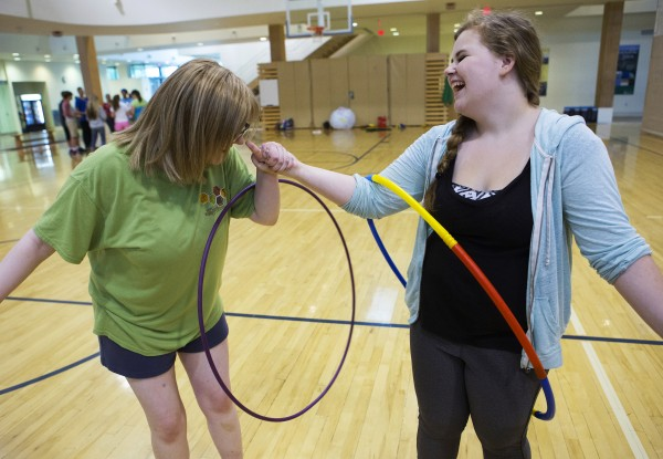 Medomak Valley's Katrina Williams (left), 15, and Charlotte Nichols, 16, work to transfer a hula-hoop around the group during a team building exercise as part of the Bridge Year program Wednesday at the Recreation and Fitness Center at the University of Maine.