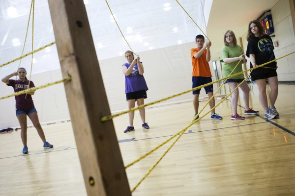 Medomak Valley students work together to navigate a piece of lumber through a rope maze during a team building exercise as part of the Bridge Year program Wednesday at the Recreation and Fitness Center at the University of Maine.
