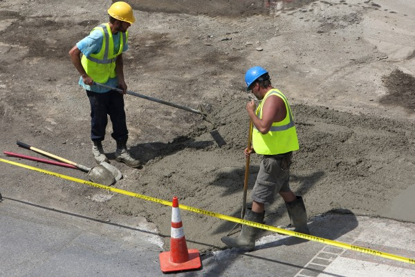 Construction workers lay concrete near the intersection of Main Street and Lincoln Street on Tuesday in Bangor.