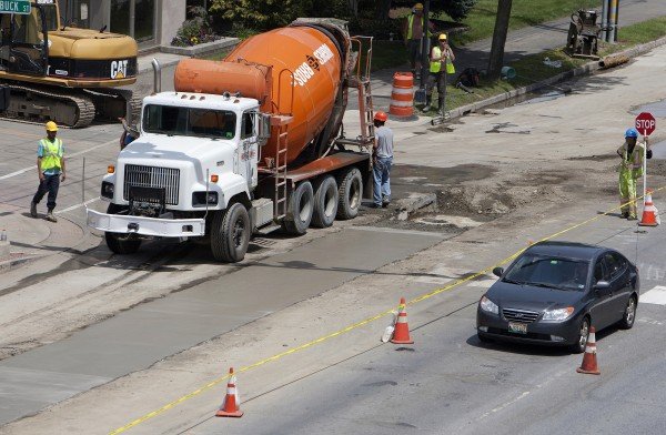 A construction crew works to lay concrete near the intersection of Main Street and Lincoln Street on Tuesday in Bangor.