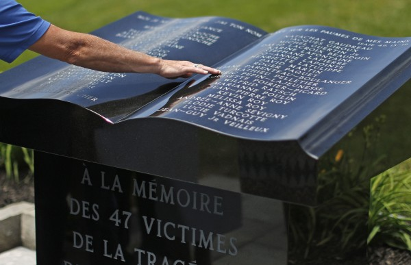 A man puts his hand on a memorial monument after a memorial mass at the Sainte-Agnes church in Lac-Megantic, July 6, 2014.