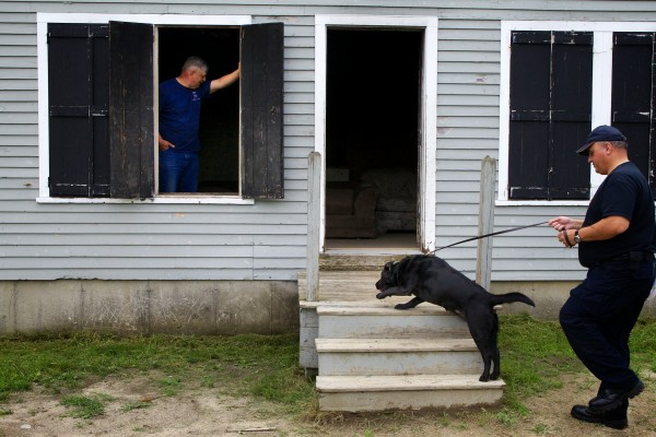 Mark Nowlan of Fredricton, New Brunswick and his fire investigation dog Mallow enter a training building during a recertification exercise on Tuesday. Paul Gallagher, who runs the training program, waits inside the building to observe.