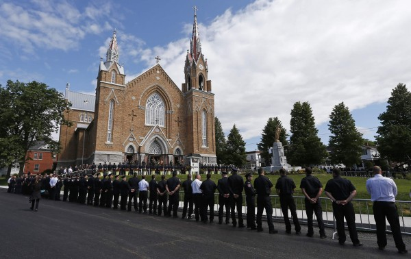 Emergency responders form an honor guard prior to a memorial mass at the Sainte-Agnes church in Lac-Megantic, July 6, 2014. The mass was held to commemorate the first anniversary of the crude-oil train explosion that killed 47 people on the morning of July 6, 2013.