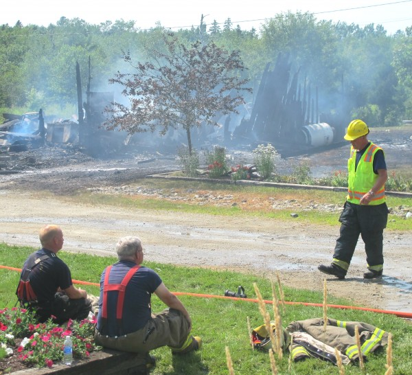 Harrington Fire Chief David Baldwin (right) walks over to two firefighters at a property on Mill River Road on Sunday afternoon while the remains of a garage smolder in the background. Baldwin said the homeowner, Joe Small, was injured in the fire but he declined to specify how he was injured or how serious Small's injuries may be.