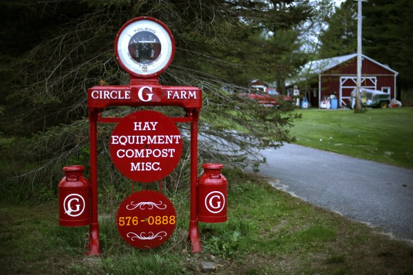 This sign for the Circle G Farm is made from a scale, milk cans and circular saw blades, and you can find it in Auburn, Maine.