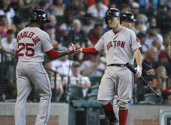 Boston's Jackie Bradley Jr. (25) is congratulated by third baseman Brock Holt after scoring a run during the fifth inning against the Houston Astros at Minute Maid Park in Houston Sunday.