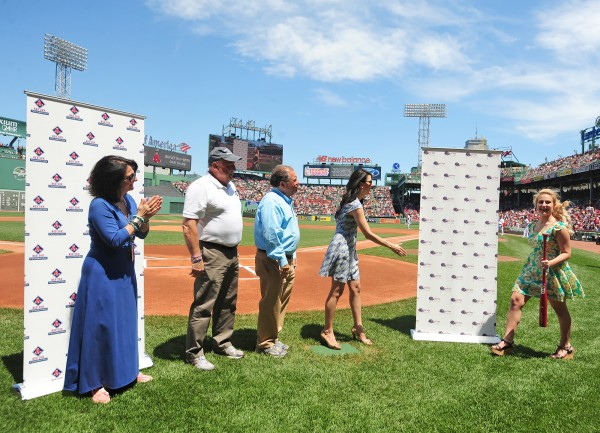 Bailey Rae-Smith (right) of Narraguagus High School in Harrington is greeted by Red Sox Foundation Board member Linda Pizzuti Henry as part of a ceremony Sunday, when the foundation presented 10 Maine students with scholarships at Fenway Park in Boston. Looking on are Red Sox Foundation Executive Director Gena Borson (left), Maine Gov. Paul LePage and Red Sox Executive Vice President Charles Steinberg.