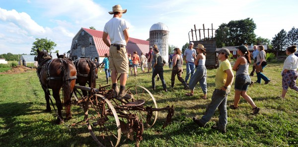 North Branch Farm co-owner Seth Yentes, left, talks about the use of horses on a farm during the Workhorse and Worksong Hootenany at the North Branch Farm in Monroe.
