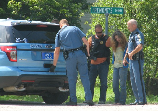 A woman believed to have been involved in a stabbing Wednesday morning in Sullivan stands with officers after they caught her behind a barn on Morancy Pond Road.