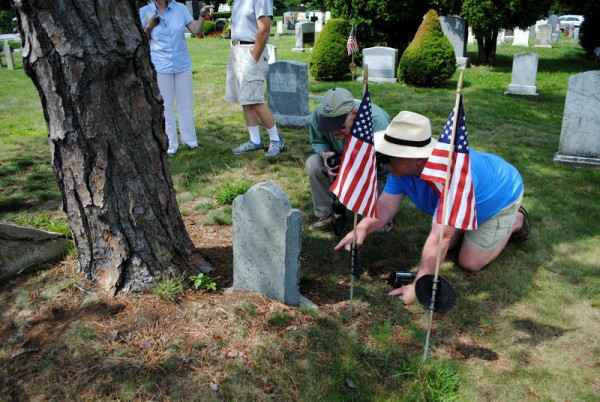 Chris Gulhaugen (right) and Warren Brayley inspect Nicholas Cushing's gravestone at Mount Pleasant Cemetery in South Portland.