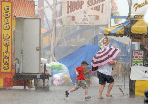 Teresa Hall of Milo and her 5-year-old nephew, Collin Hall of Millinocket, run through a downpour at the Bangor State Fair on Monday afternoon.