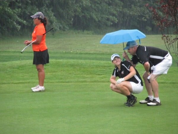Bailey Plourde of Newcastle lines up her putt as her dad and caddie, Bob Plourde, holds an umbrella on the 18th green during Monday's Maine Women's Amateur golf tournament at Waterville Country Club in Oakland. Ruth Colucci of Biddeford-Saco Country Club looks on.