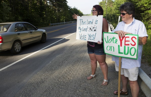 Deanna Lee (left) waves to passing cars while showing her support of the land use ordinance amendments with Jane Logan on Tuesday at the Town of Clifton Municipal Office.