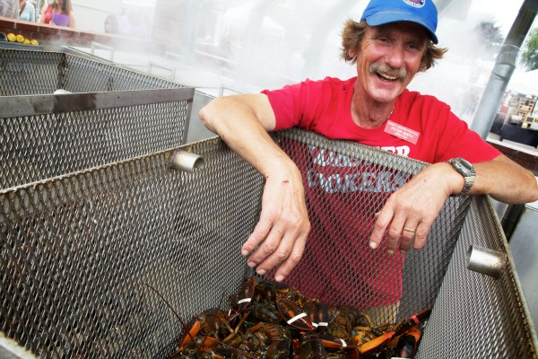 Local lobster cooking legend Peter Smith leans over a basket of doomed crustaceans at the 67th annual Maine Lobster Festival in Rockland on Wednesday. Smith has been serving up steamed lobster at the festival since 1972.