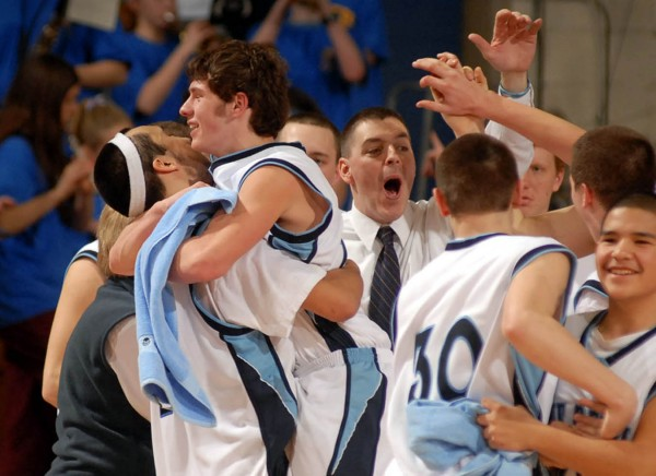 Members of the Calais Blue Devils and coach Ed Leeman (center) celebrate their 62-59 victory over Piscataquis Community in the Eastern Maine Class C final at Bangor Auditorium in this February 2007 file photo.