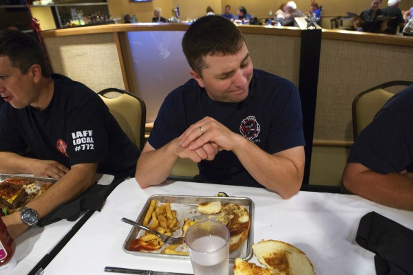 Bangor firefighter Jesse Bieluch cringes from eating so much burger during an eating contest Tuesday at Hollywood Casino's Celebrity Bar & Grill in Bangor.