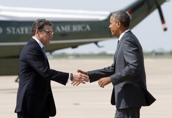 President Barack Obama is greeted by Texas Governor Rick Perry upon Obama's arrival in Dallas on Wednesday to discuss a surge of Latin American young people crossing the U.S.-Mexico border.