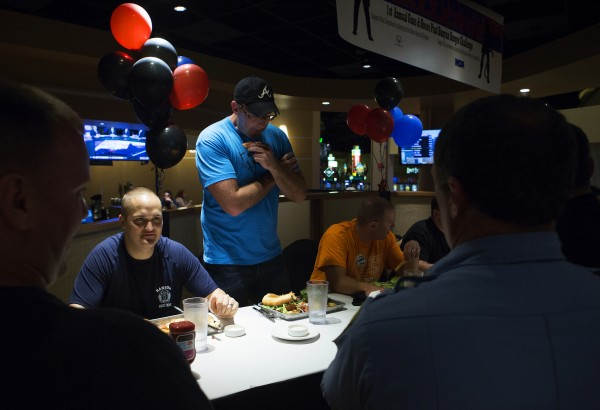 Bangor police Officer Aaron Brooker (center) stands up to try to help make room during a burger-eating contest Tuesday.
