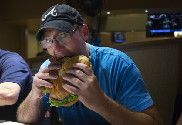 Bangor police Officer Aaron Brooker digs into his burger during a burger-eating contest Tuesday at the Celebrity Bar & Grill.