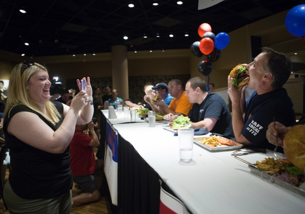 Laura York (left) takes a photo of Lt. Greg Hodge of the Bangor Fire Department during a burger-eating contest Tuesday at the Celebrity Bar & Grill at Hollywood Casino in Bangor. The Guns & Hoses Paul Bunyan Burger Challenge put five members of the Bangor Police Department up against five members of the Bangor Fire Department for charity on the eve of the restaurant's grand opening . The Bangor firefighters won, leaving only four and three-quarter pounds of food left, compared with Bangor police's five pounds.