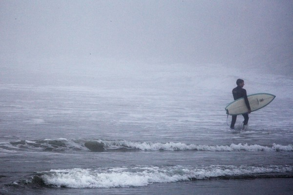 A man, carrying a surfboard, trudges through the waves at Higgins Beach in Scarborough on Wednesday.