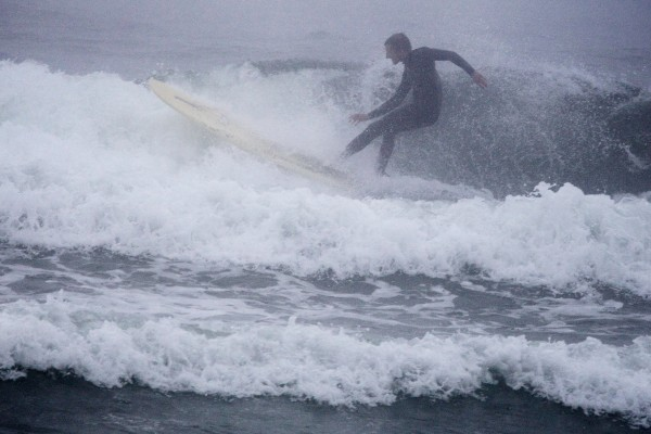 A surfer catches a wave in the fog at Higgins Beach in Scarborough on Wednesday.