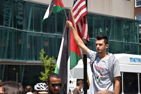 Nimer Farhood, 19, of Portland raises a Palestinian flag into the air as he stands above the crowd gathered in Monument Square.