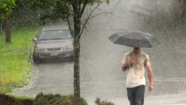 A man walks through a parking lot during a downpour in Bangor on Wednesday.